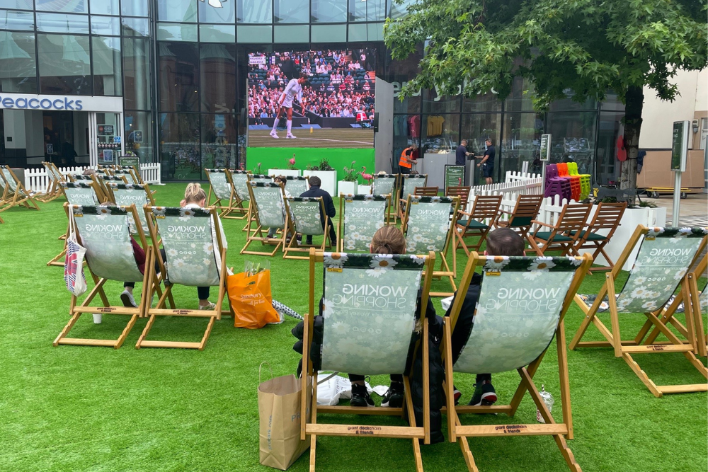 People sitting in deckchairs watching the tennis on a big screen in Jubilee Square, Woking town centre